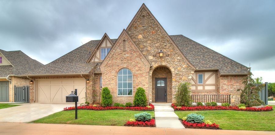Exterior of home with beautiful landscaping and stone and brick.