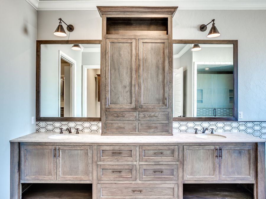 His and her sink with wood cabinets.