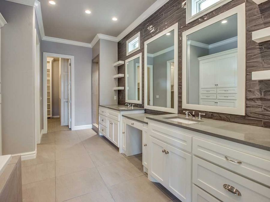 Master bathroom with his and her sink against a beautiful tile wall.