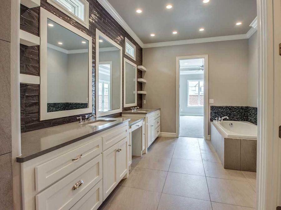 Master bathroom with stone pebble back splash around tub.