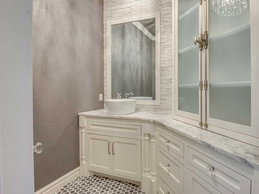 Powder room with large white cabinets and tile wall.