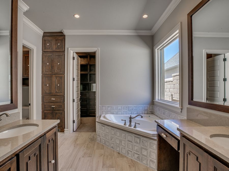 Master bathroom with luxurious tub and tall cabinets.