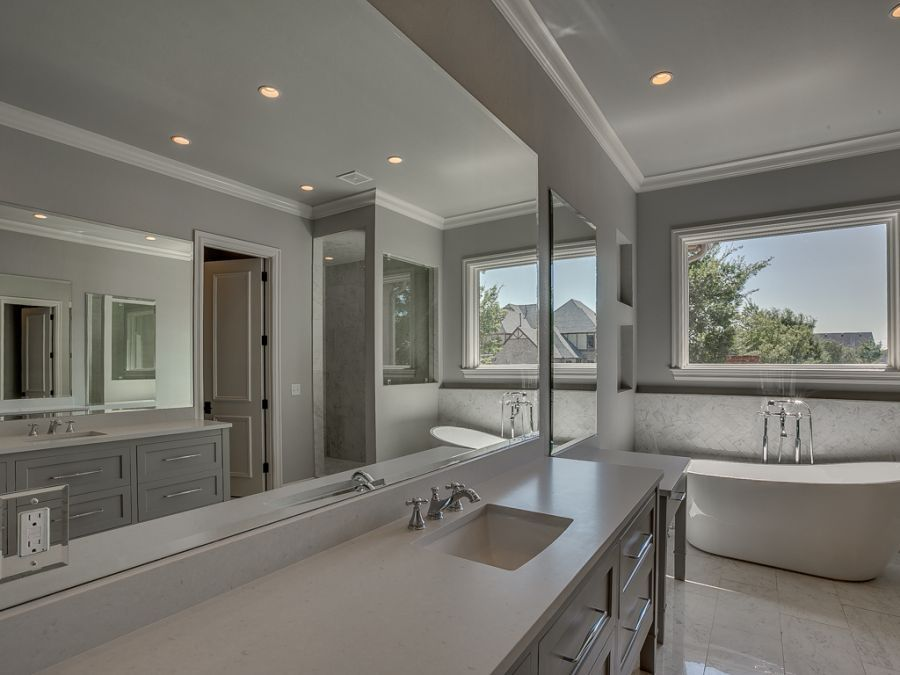 Master bathroom with large mirrors and natural lighting.