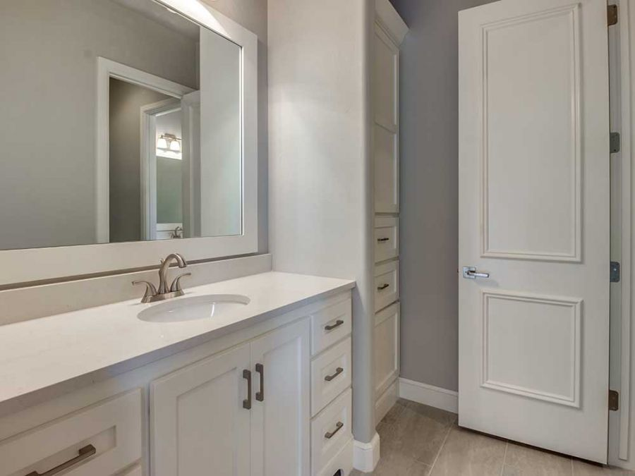 Guest bathroom with eloquent tile and white cabinets.