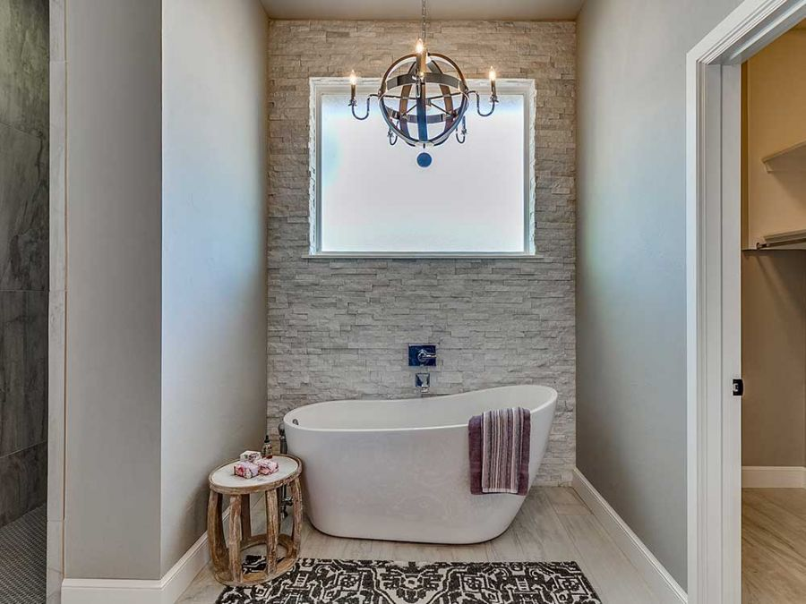 Beautiful tile tub and eloquent chandler in master bathroom.