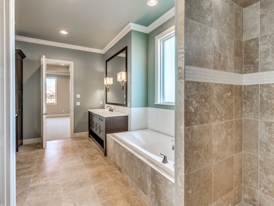 Master bathroom with dark wood cabinetry and beautiful tile flooring.