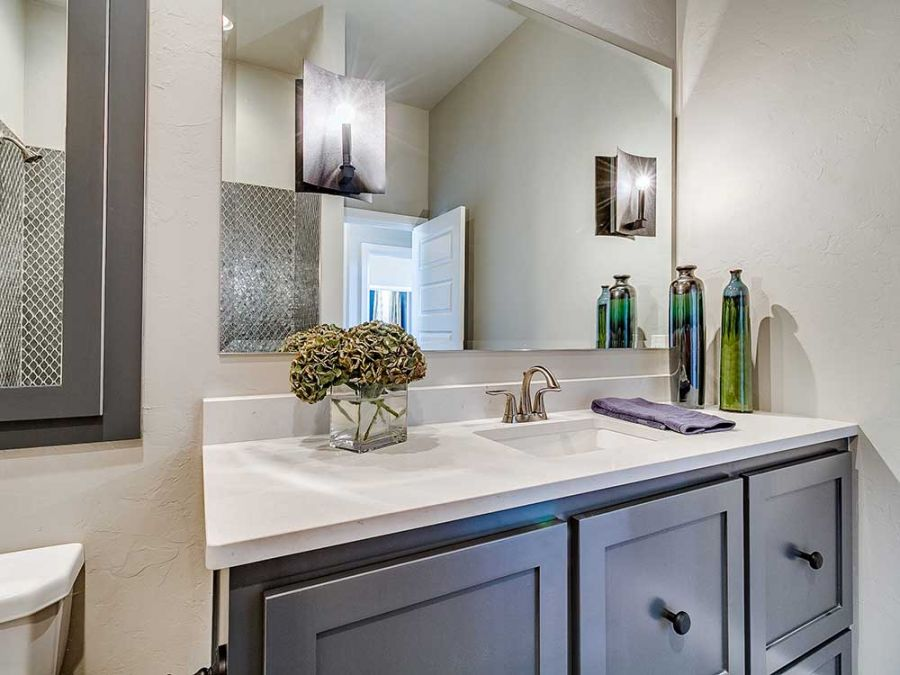Guest bathroom eloquent gray cabinets and white counter top.
