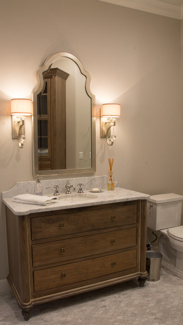 Guest bathroom with beautiful marble vanity and marble tile flooring.