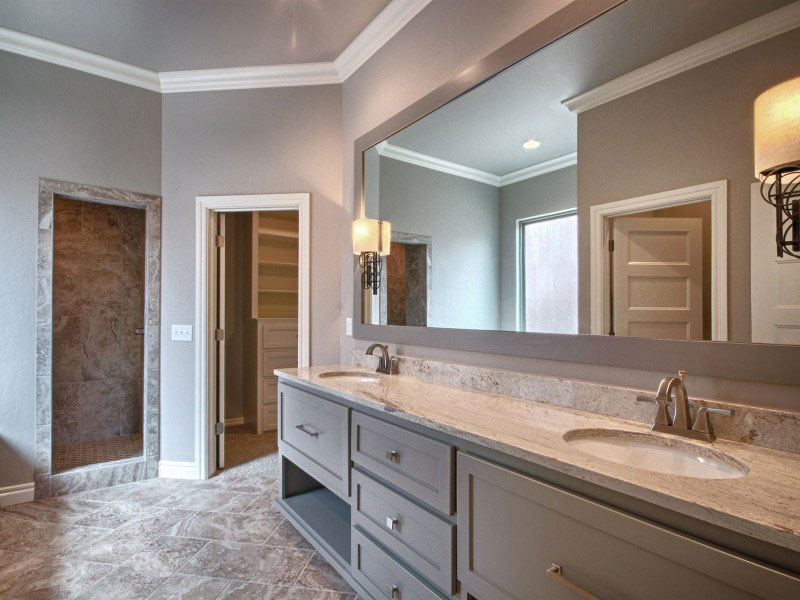 Luxurious master bathroom with beautiful tile flooring, shower, and double sinks.
