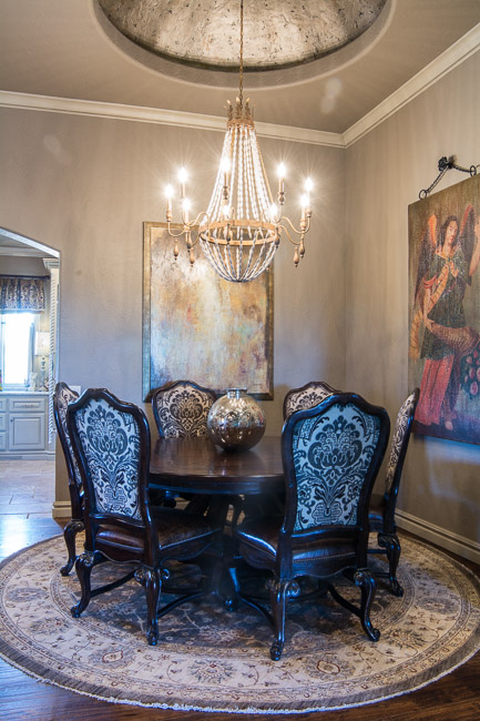 Elegant dining area with chandler and round rug.