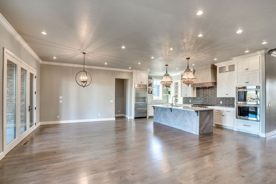 Dining area next to kitchen island and large windows with door leading to back patio.