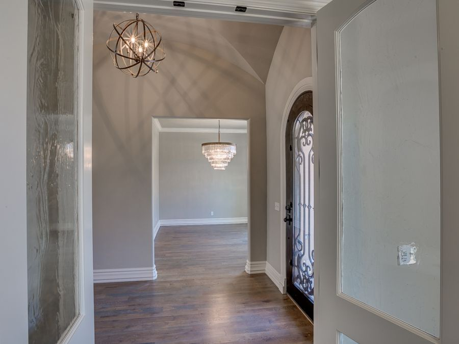 Large entryway with gorgeous wood and glass door that features designed iron work.