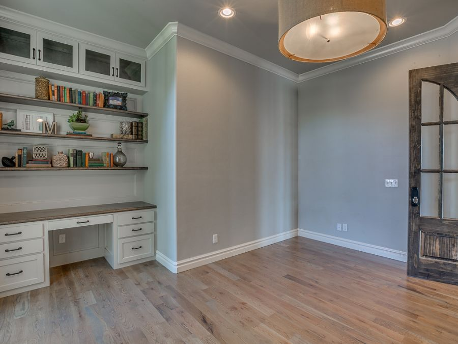 Entry way leading into the perfect study with built in desk and book shelves next to large windows for natural lighting.