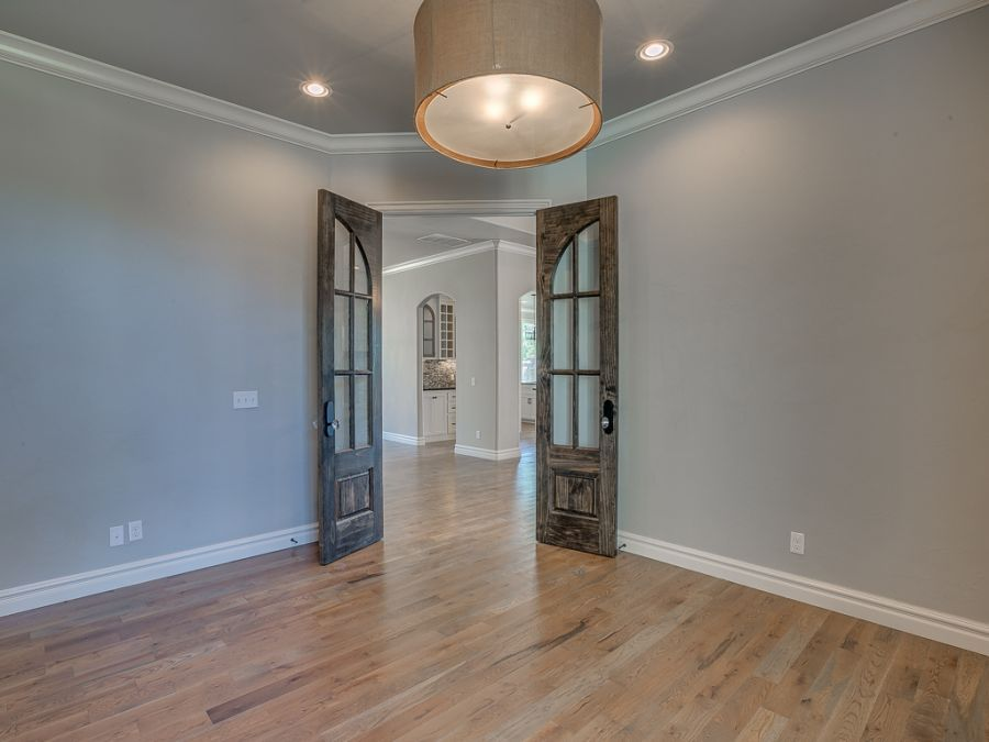 Entryway leading to room with unique rustic doors and beautiful wood floors.