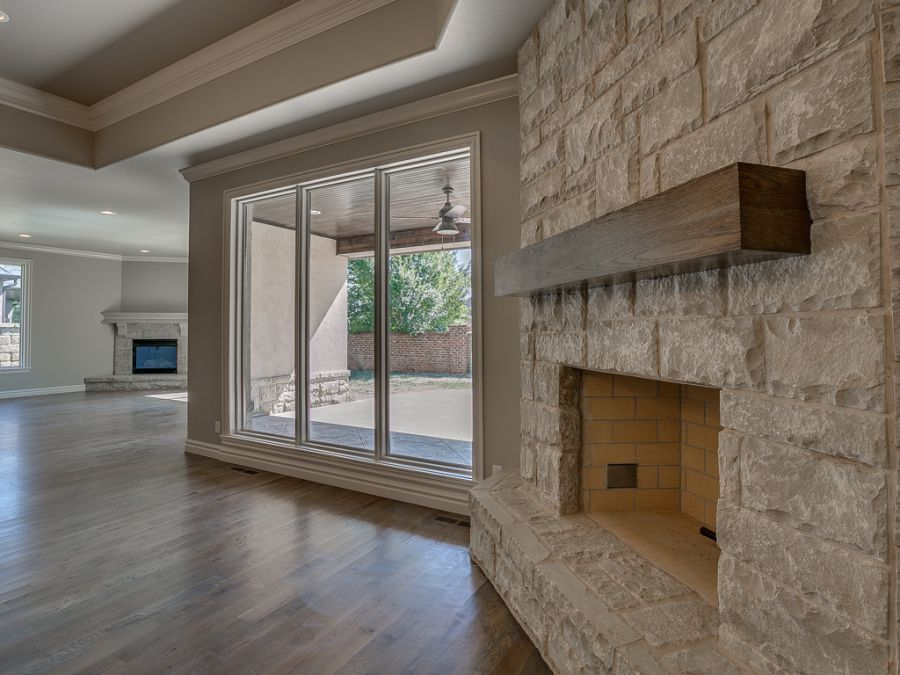 Entry of living area with real wood fire place made of stone that is across the room from gas fireplace. All rooms are centered around the covered outdoor living area.
