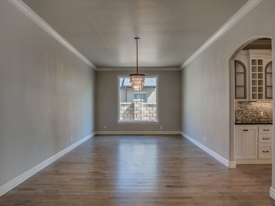 Dining area entry with beautiful chandler and large windows for natural lighting.