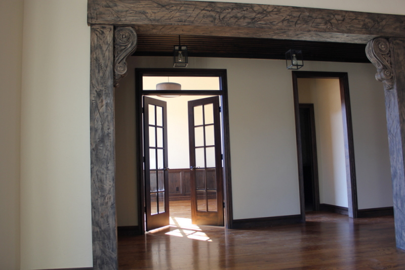 Grand entry with large wood pillars around doorway in home by Bill Roberts Custom Homes.