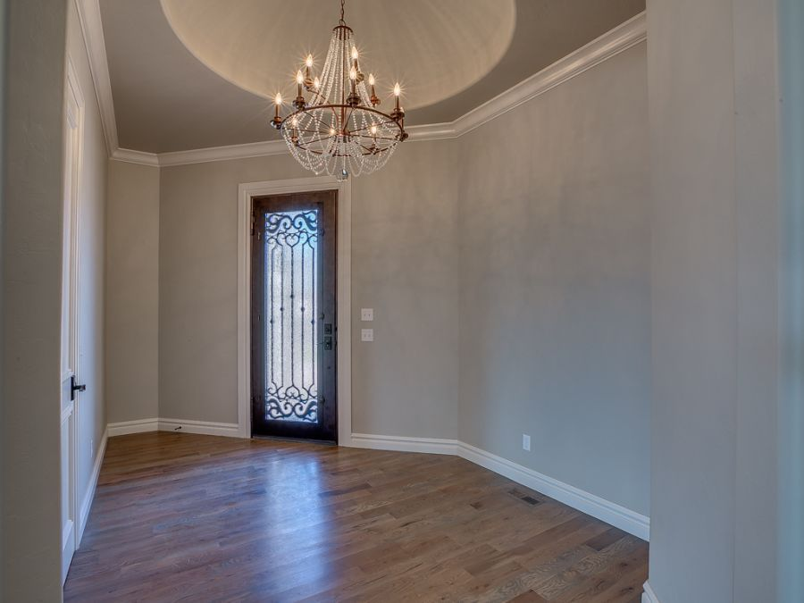 Quaint entry hallway with beautiful wood and glass door with iron work.