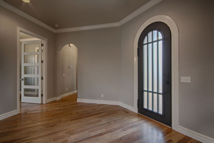 Large entry door with light wood flooring at entryway.