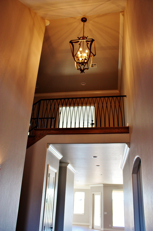 Entryway with high ceiling and rustic chandler in home by Bill Roberts Custom Homes.