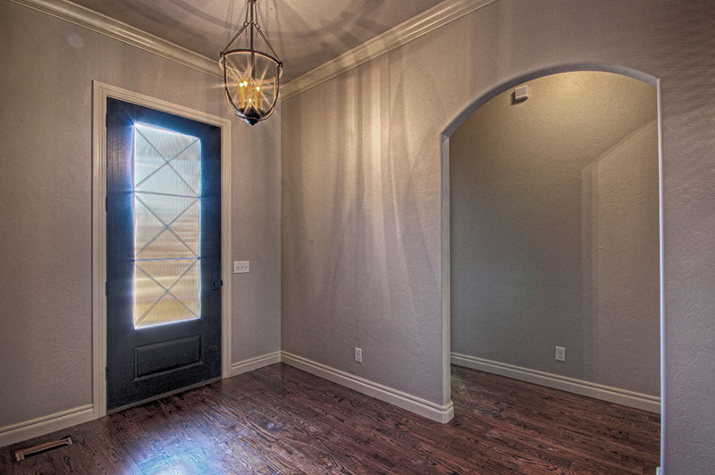 Entryway with dark wood flooring and chandler in a large hallway.