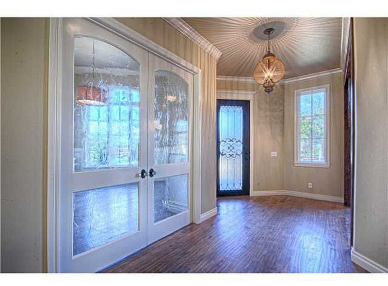 Extravagant entryway with large chandler and door with ironwork.