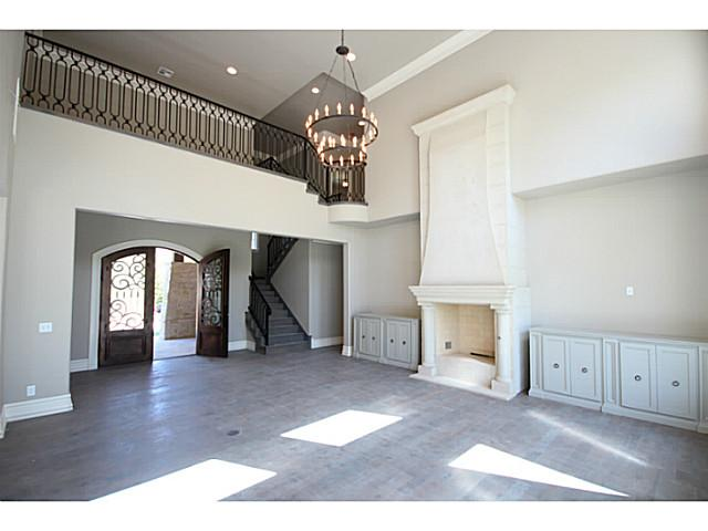 Double door entry made of wood and glass with beautiful iron work that leading into the grand living room.
