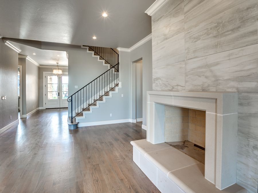 Entry way with beautiful big white double doors that leads into living room by Bil Roberts Custom Homes.