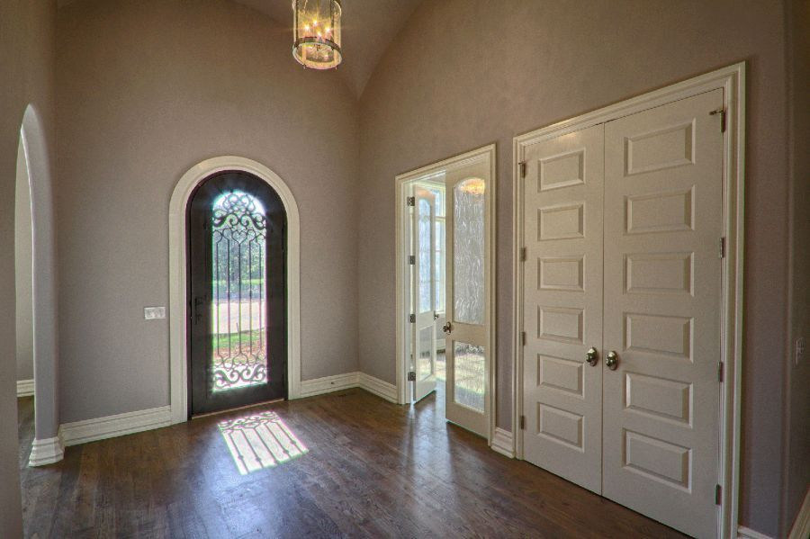 Entrance door with beautiful ironwork and hallway leading to the study and dining area.
