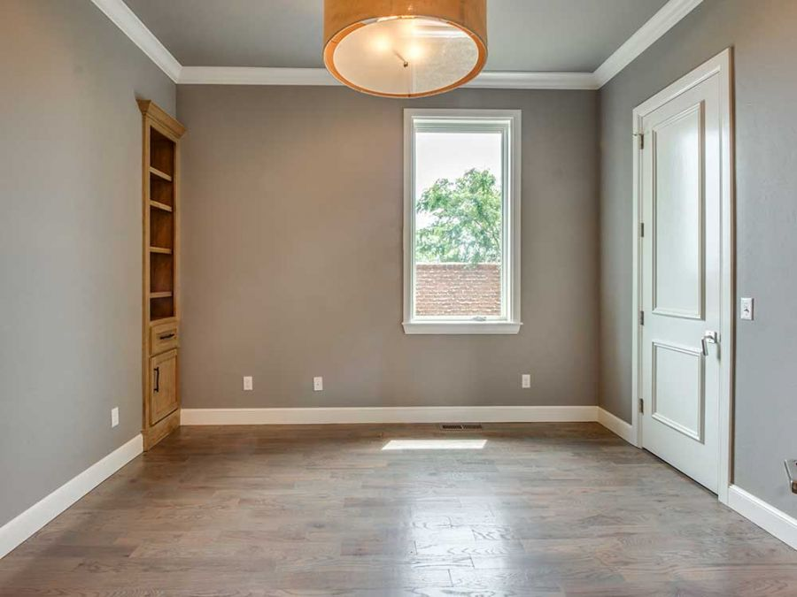 Beautiful room with wood flooring and chandler. Bookcase built into wall.
