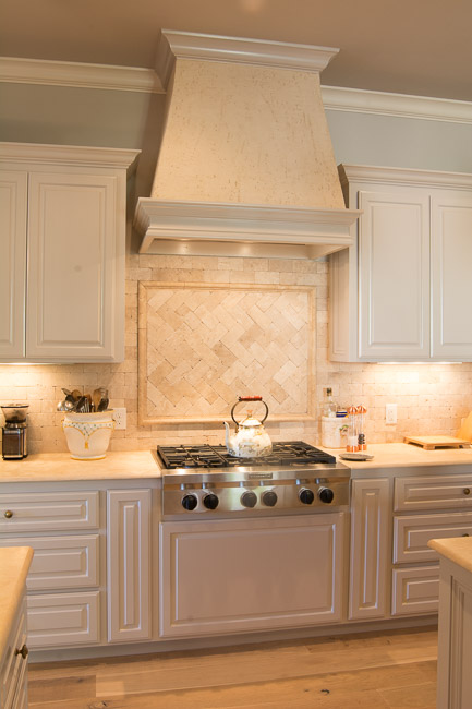 Kitchen gas stove with cream stone tile backsplash and white cabinets.