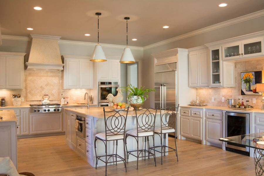 Big kitchen with white cabinets and an antique white tile backsplash.