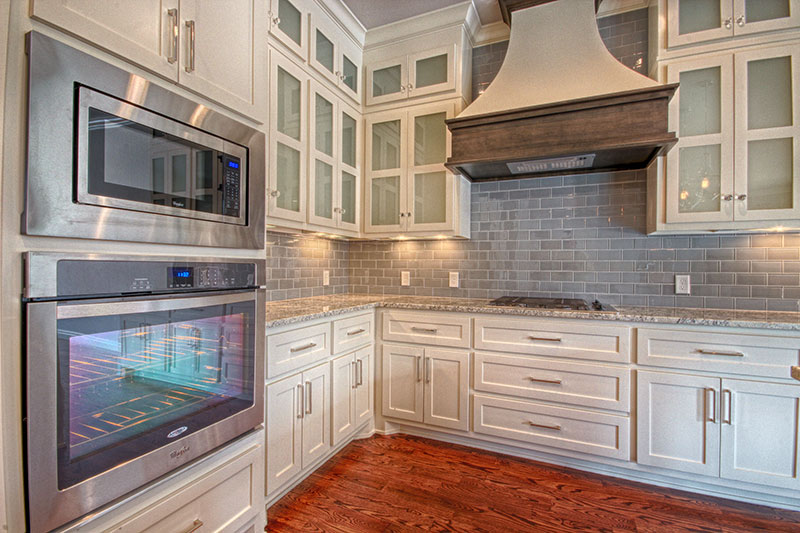 Beautiful kitchen with a large vent over the stove.