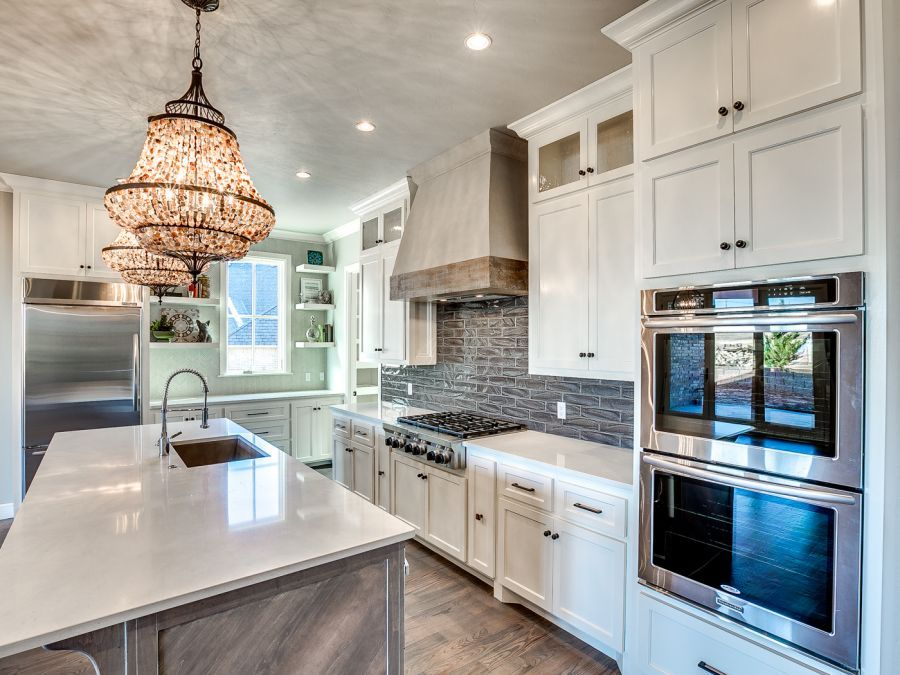 Luxurious kitchen with two gorgeous chandlers above the large island.