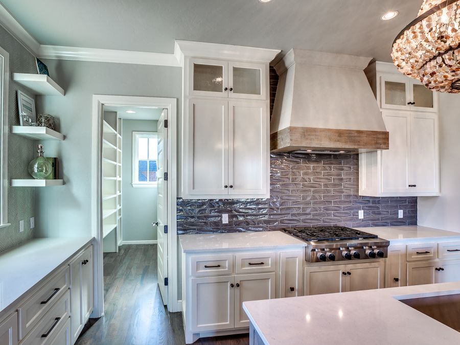 White cabinetry and gray tile backsplash with beautiful white counter tops.