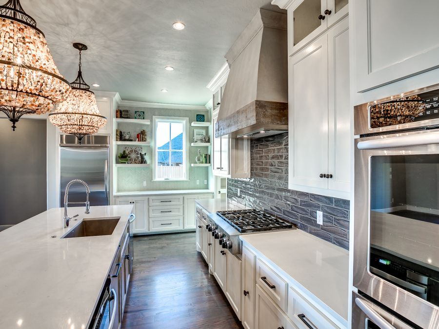 Stainless steel appliances with white cabinetry and beautiful wood flooring.