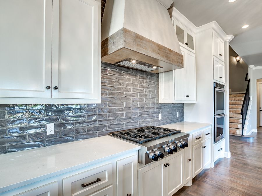 Kitchen with beautiful stainless steel stove and vented hood with wood decor.
