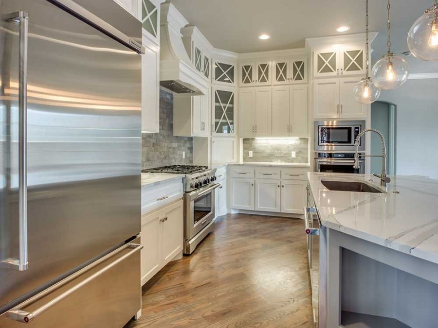 Kitchen with white counter tops that have beautiful gray streaks in it.