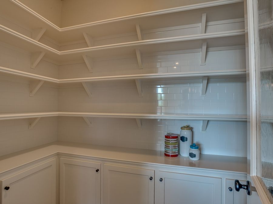 Walk in kitchen pantry with plenty of shelves and cabinets for storage.