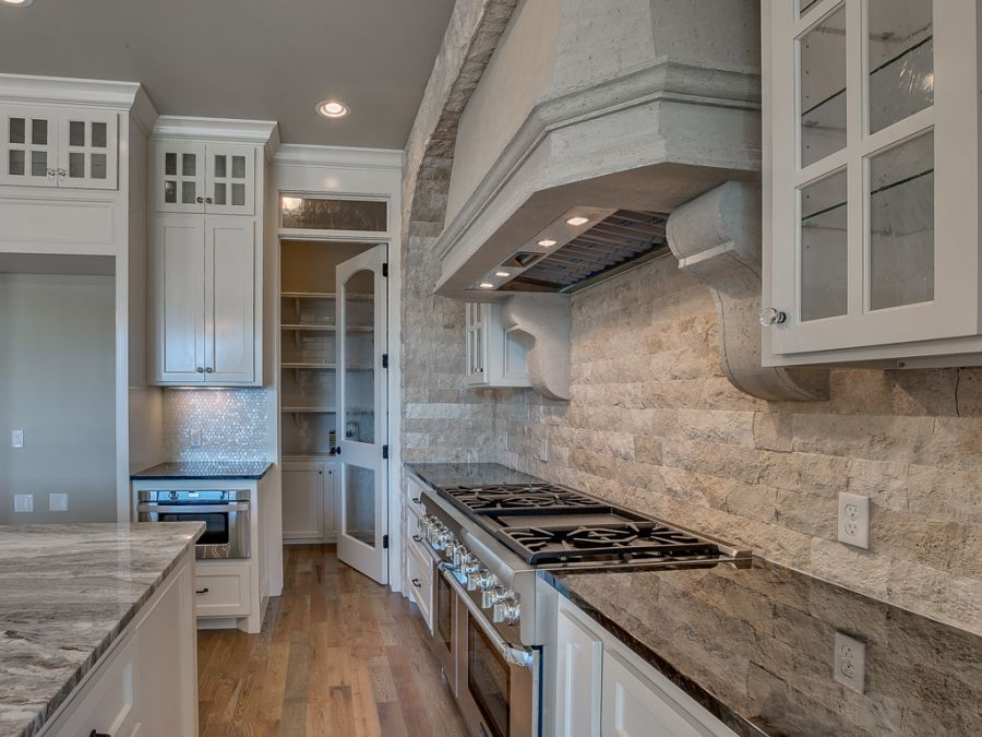 Long range view of stove area that has a antique white stone wall and black counter tops.