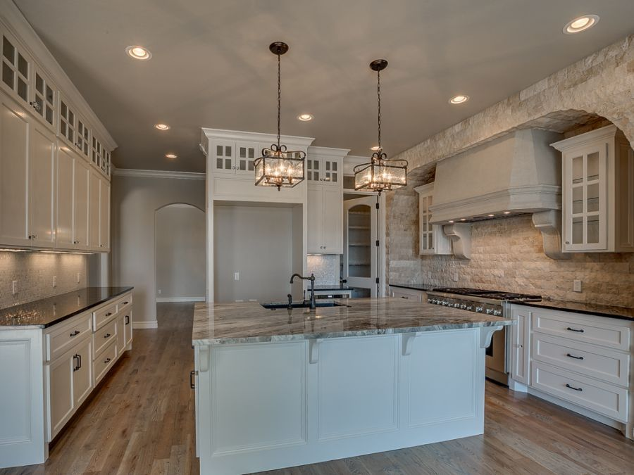 Full view of kitchen with beautiful white cabinets and wood flooring.