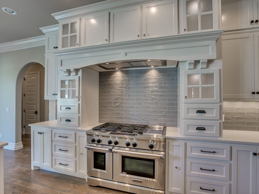 White cabinets with plenty of storage around the stove and oven area for spices.