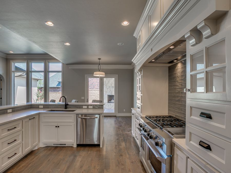 Beautiful spacious kitchen with open floor design and outdoor fireplace in view.