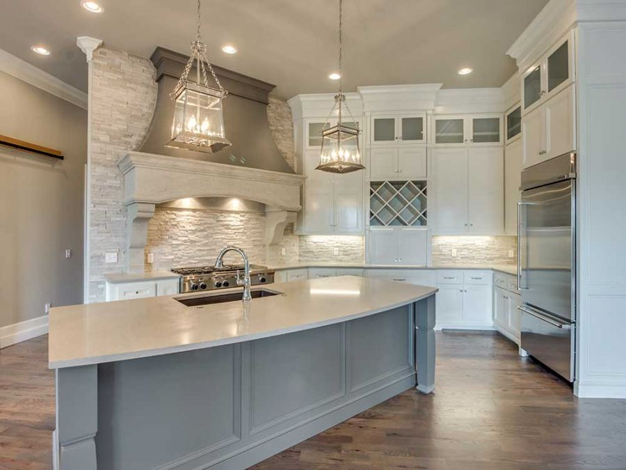 White cabinets with wine storage against a beautiful tile wall.
