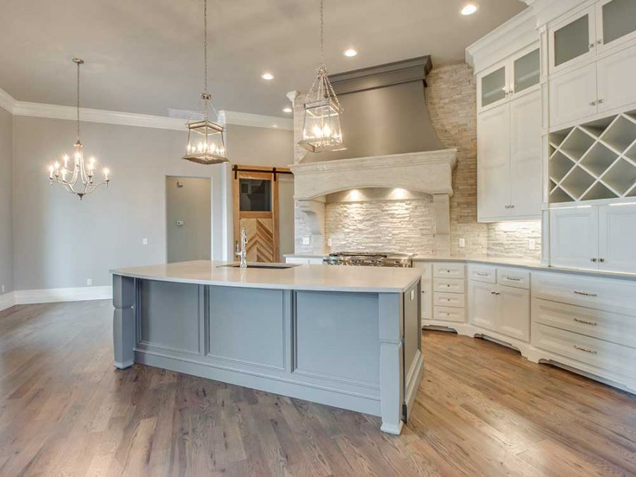 Open kitchen design with luxurious wood flooring and beautiful chandlers.