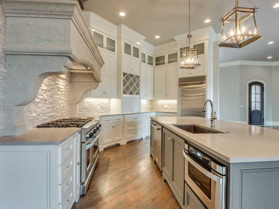 Beautiful concrete decor above oven and stove that hides a large vent for cooking.
