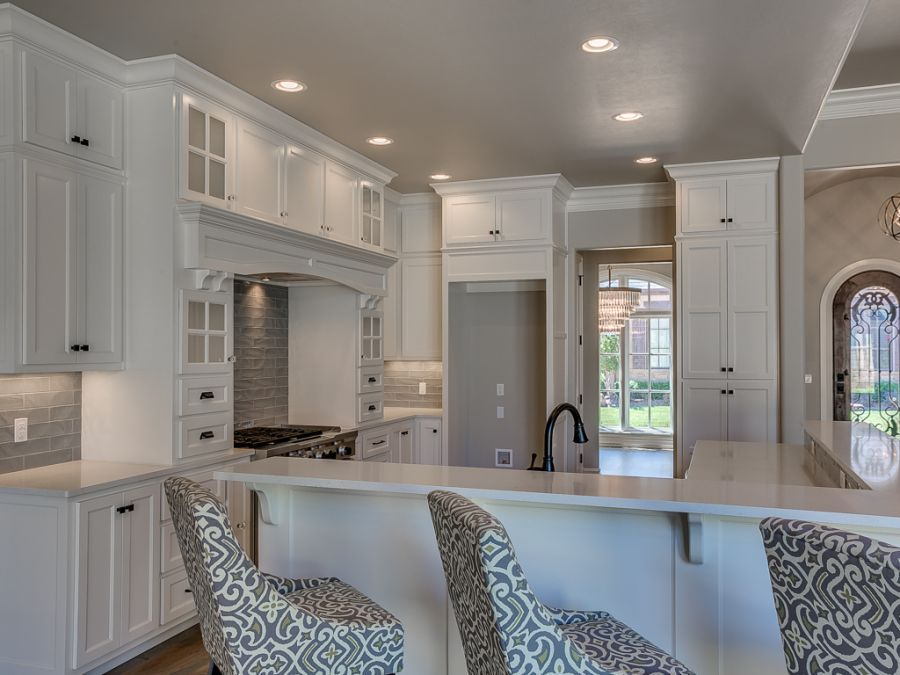 Large white cabinets with L shaped island that has a high seating area.
