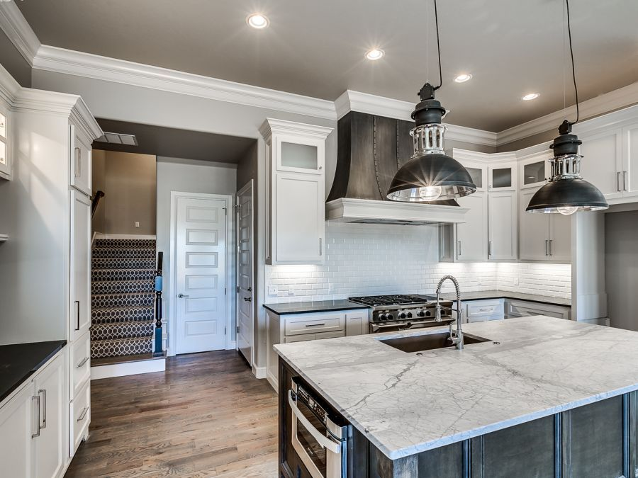 Full view of luxurious rustic kitchen that has white and clack counter tops.
