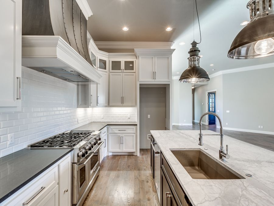 White cabinets in a beautiful kitchen area with gray and white counter tops on the island and black counter tops on the everywhere else.