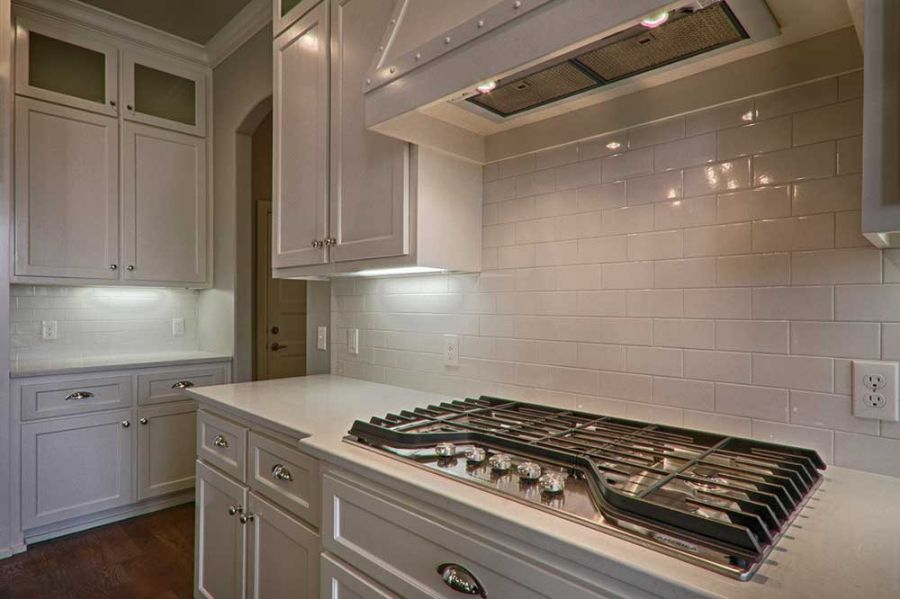 Gas stove with white tile backsplash and plenty of counter space.